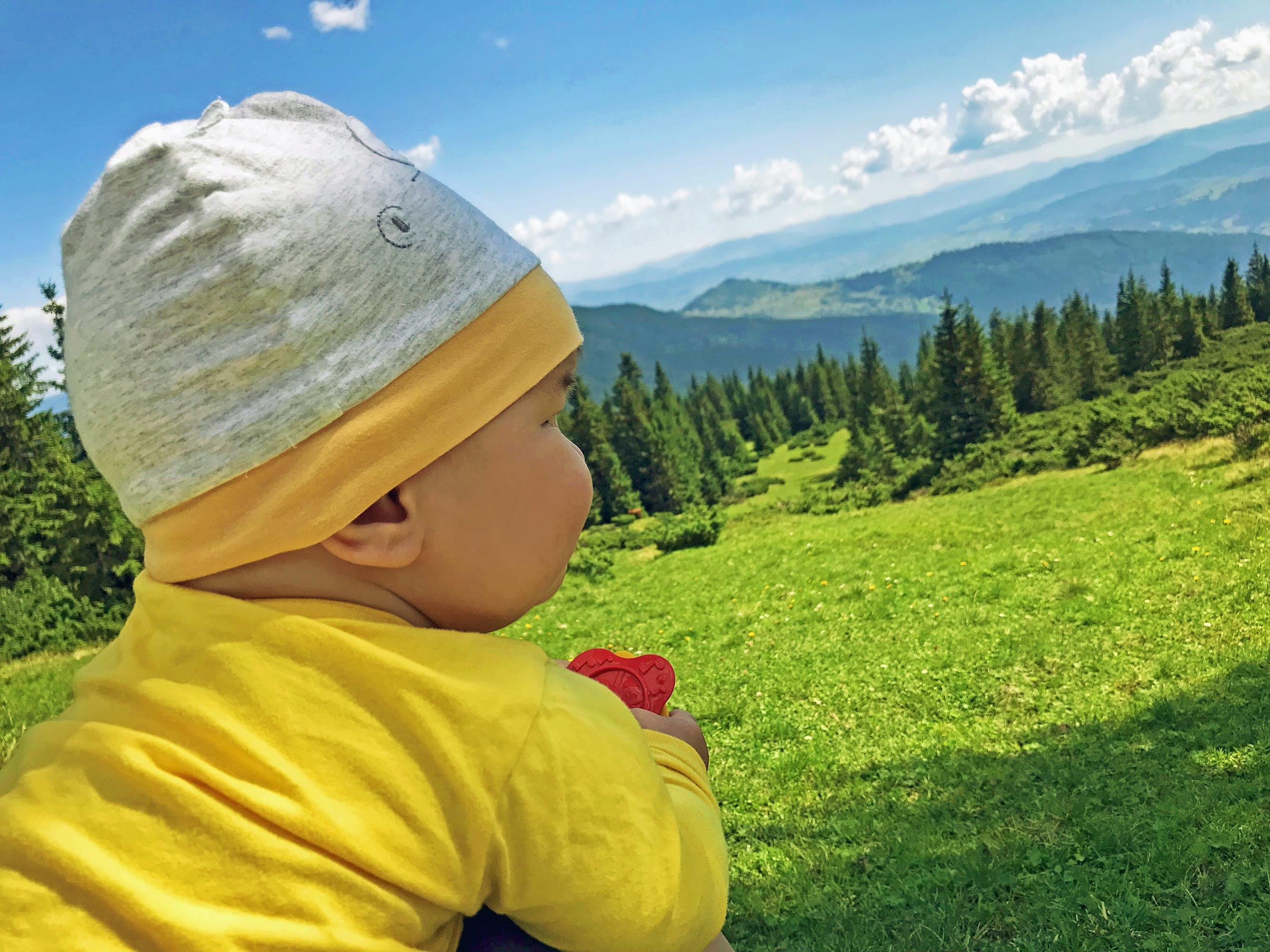 A very young baby wears bright yellow pajamas and a knit hat as he looks out on a mountain vista; kids outdoors adventures