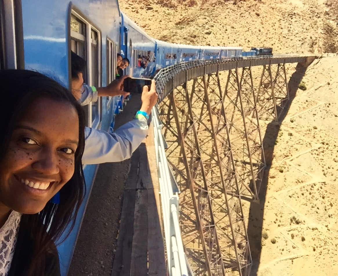A woman with her head out of a train window smiles at the camera. In the background a number of people are also sticking their heads out of the train's windows to take selfies