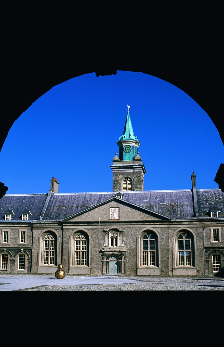 Exterior shot of the stone Irish Museum of Modern Art. There is a green steeple at the top of the museum.