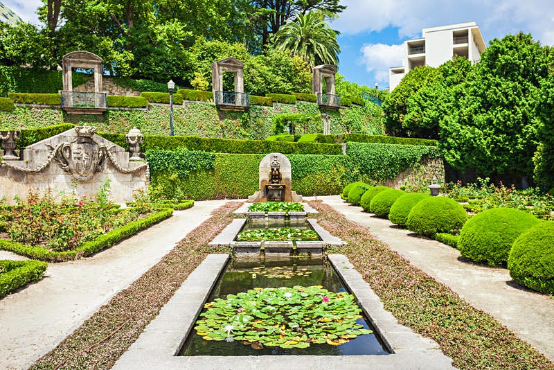 Three ponds filled with lily pads sit end to end, with a fountain at the end; heavily manicured hedges and shrubs fill the remainder of the garden, with ivy climbing up the walls at the end where there are three Juliet balconies.