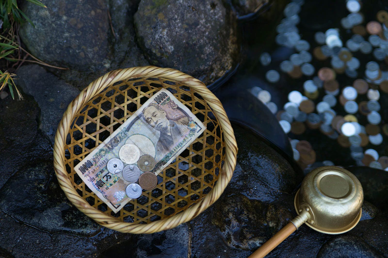 Money at the Zeniarai Benten Shrine in Japan; it is said money that is washed in the water here will double