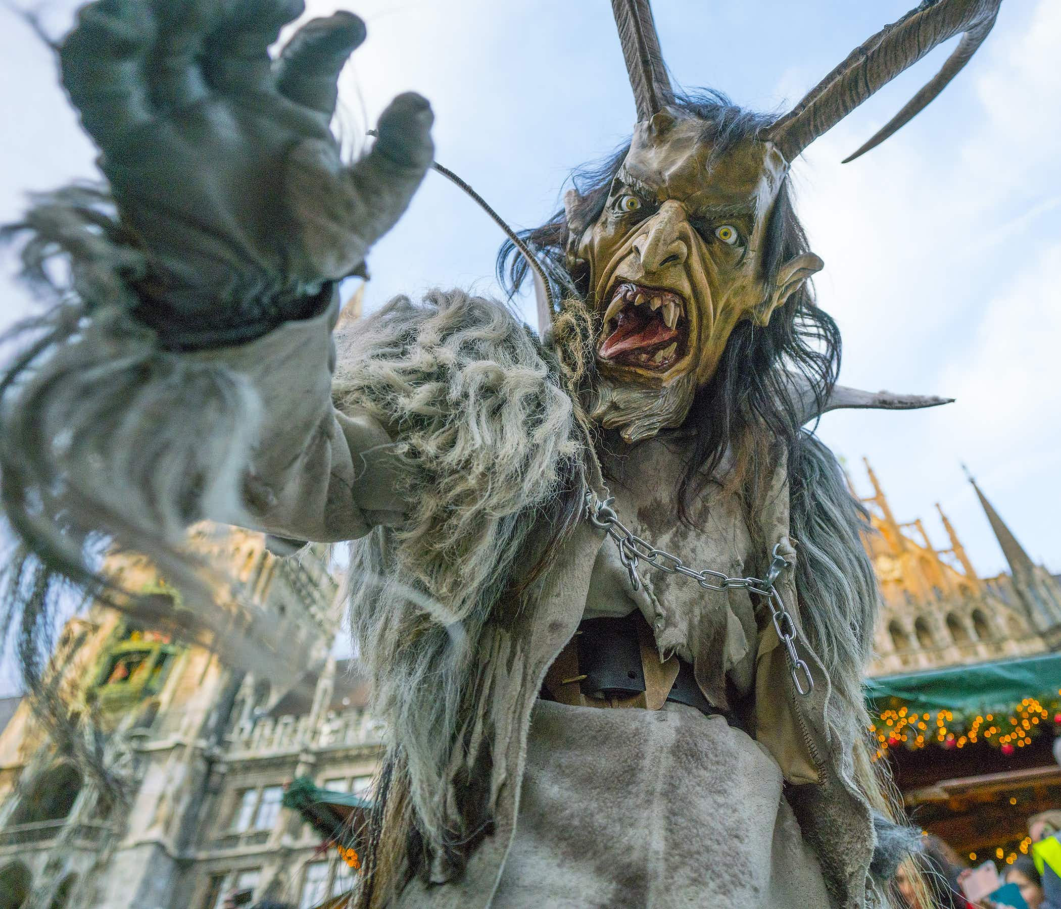 A person dressed as Krampus, the Christmas demon, reaches for the camera while exposing a large tongue and pointy teeth. The Krampus costume also features two large horns protruding from the head and a hairy body
