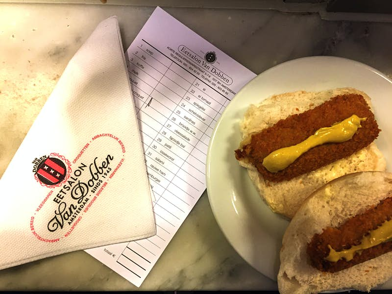 On the right is a bread roll split in half; each slice is topped with a kroket and a line of yellow-brown mustard. On the left is a napkin folded diagonally, displaying the name of the cafe (Eetsalon Van Dobben).