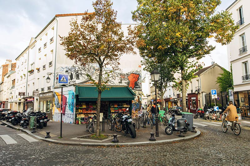 A street scene in Butte aux Cailles, Paris. A fruit and vegetable store covered in colourful graffiti stands on the corner of a cobblestone road, with cyclists and pedestrians passing by.
