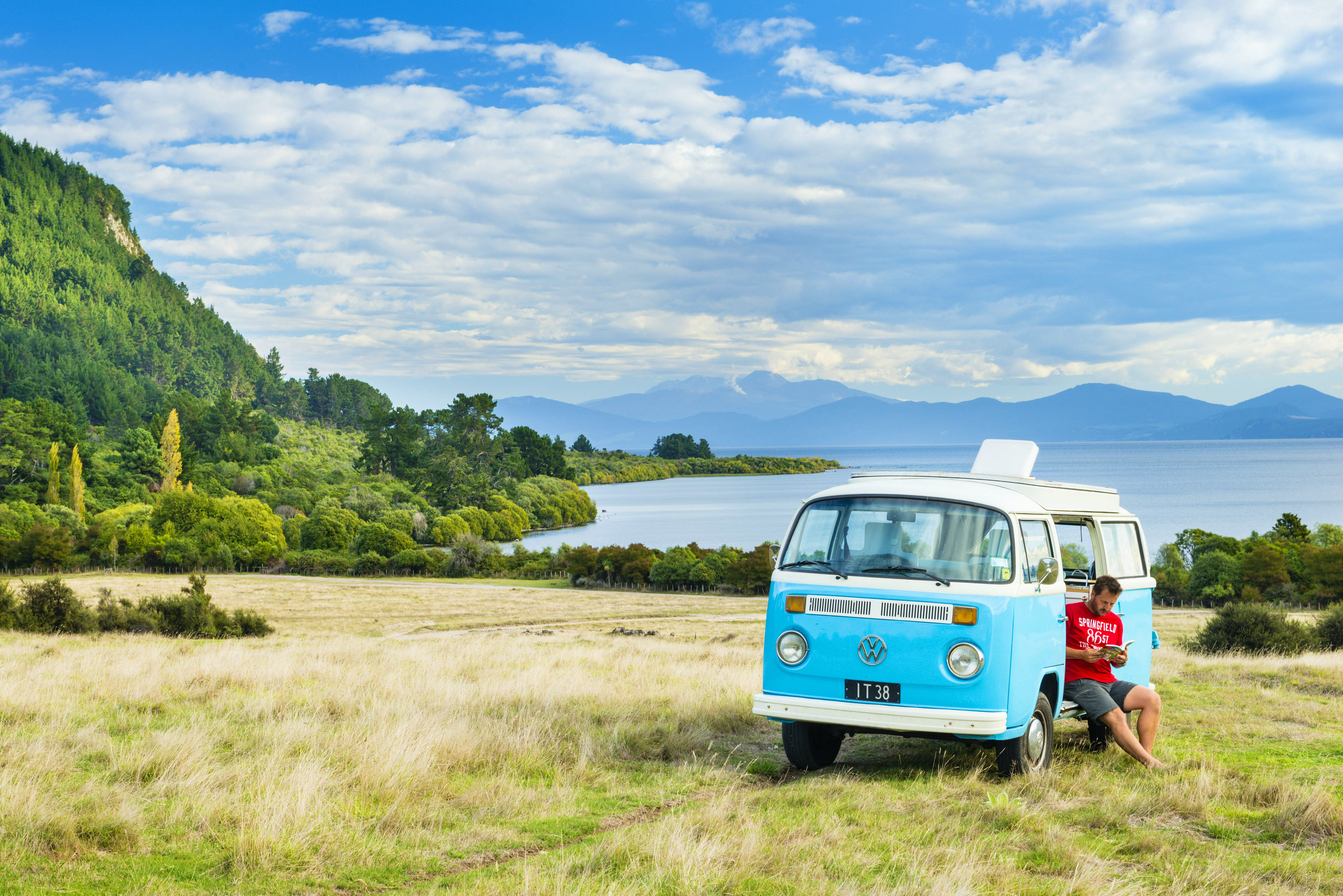 A man in a red T-shirt is sitting in the open door of a bright blue VW campervan reading. The can is parked on grassy terrain beside a beautiful lake lined with green trees.