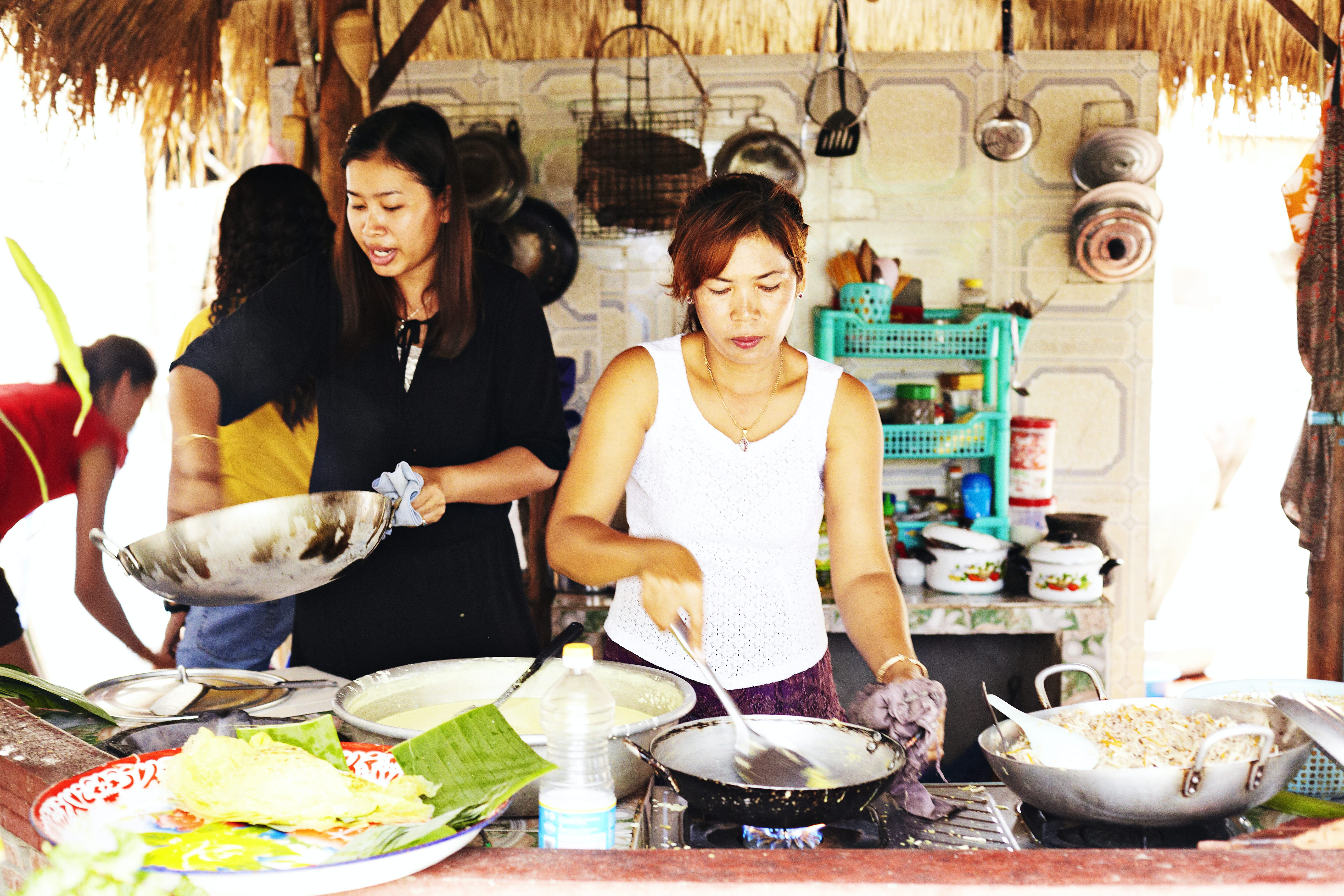 A group of women are cooking up a feast in a homestay. There are many woks on a stove, and behind them there's lots of cookware hanging from the wall, and sitting on a counter.