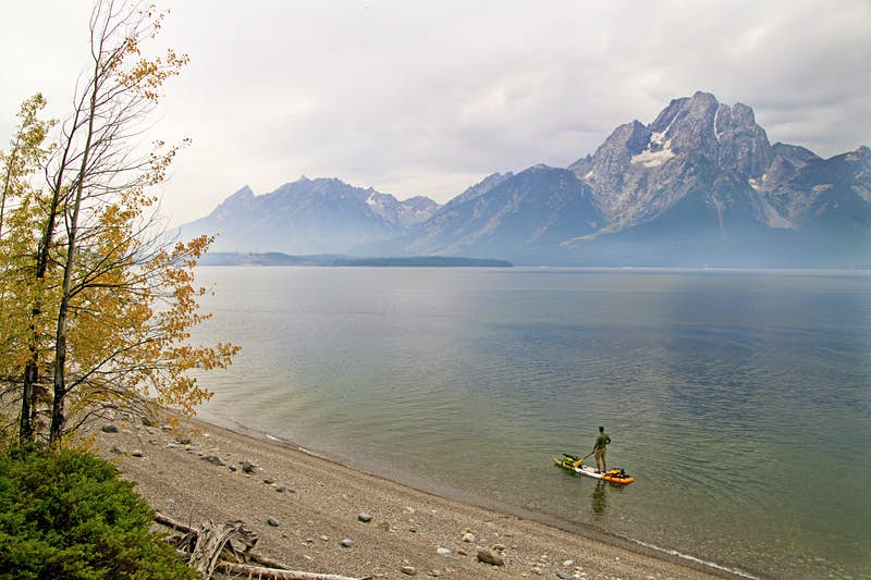 A man paddles a paddleboard across a misty lake with a mountain rising in the background at Grand Teton National Park; Stand up paddle boarding