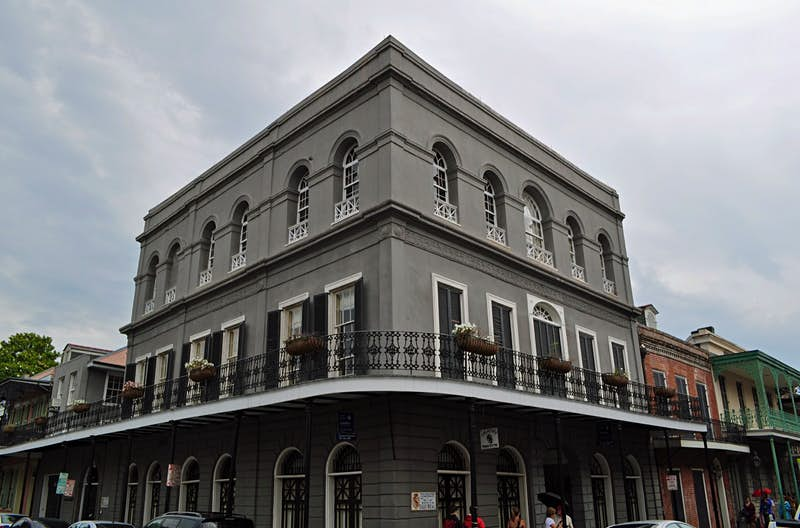 External shot of the slate gray LaLaurie Mansion with its metal railings lined with flowers; haunted places world