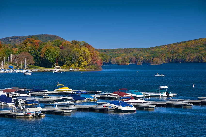 Boats are moored at a marina in a brilliant blue lake in autumn, with fall colors on the lake shores; New England fall foliage road trip
