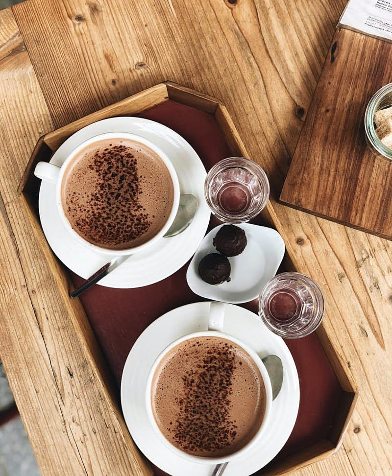 Plain white mugs of hot chocolate sprinkled with spices and more chocolate on wooden trays arranged on warm wood tables with knots and wood grain visible.