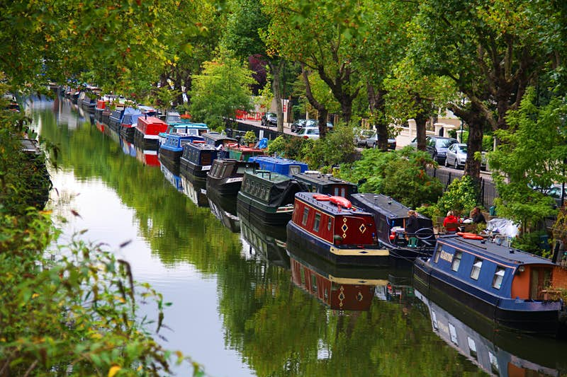 Two rows of house boats line the edge of a canal wall. Trees flank the paved walkway and a group of people sit on a wooden bench; Heathrow Layover