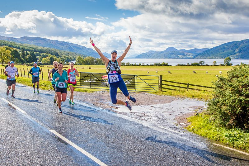 Half a dozen competitors run along a wet section of road along a farmer's field dotted with sheep; one runner is leaping in the air, with arms raised and heels clicking together. In the background are rolling green hills and Loch Ness.
