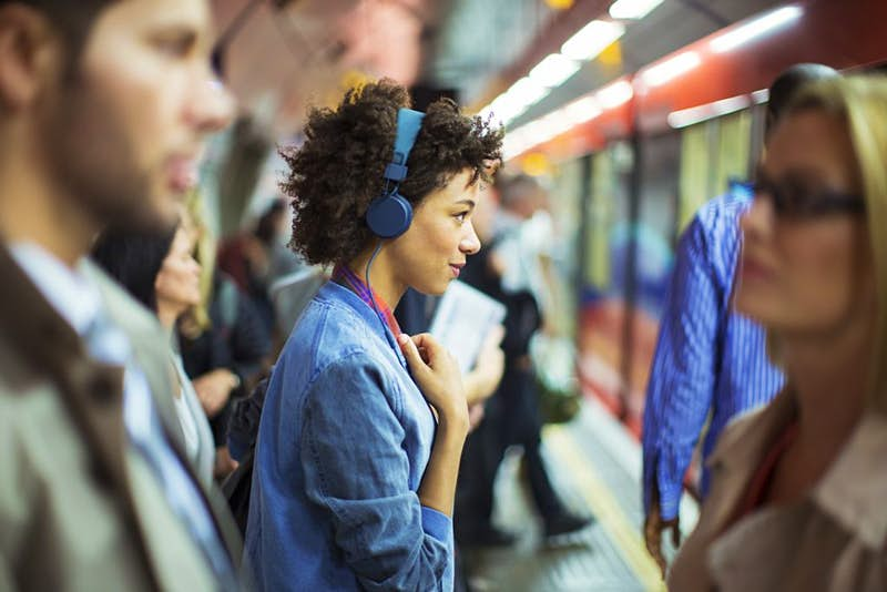 A woman listening to music on the London Tube