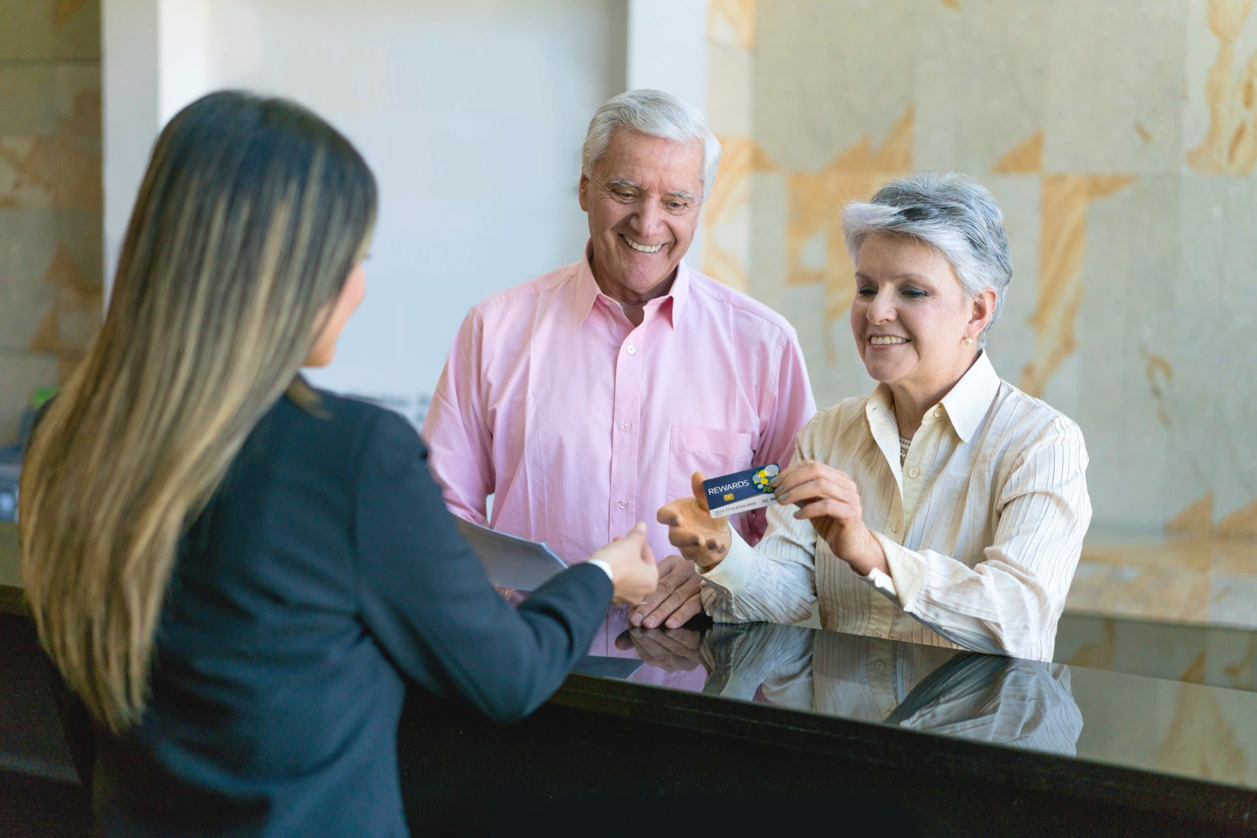 An older couple handing a card to a hotel receptionist