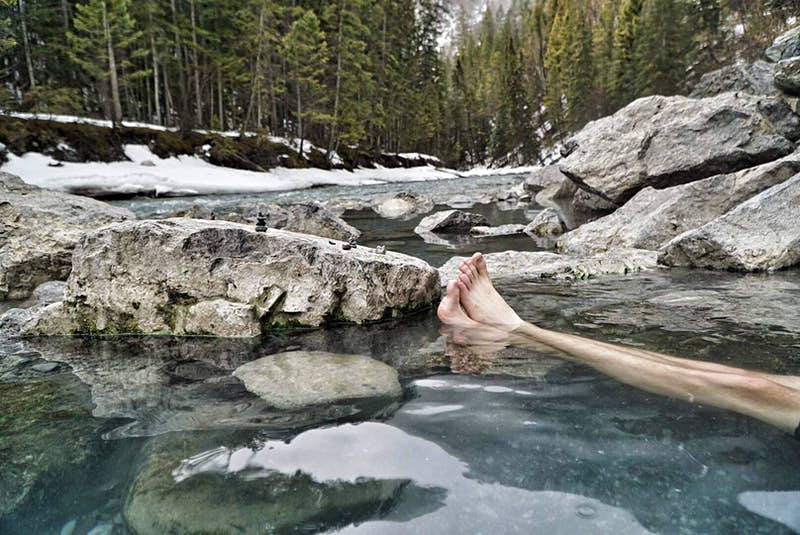 A person is sitting in a rocky pool, in the middle of a forest; only their crossed legs are visible.