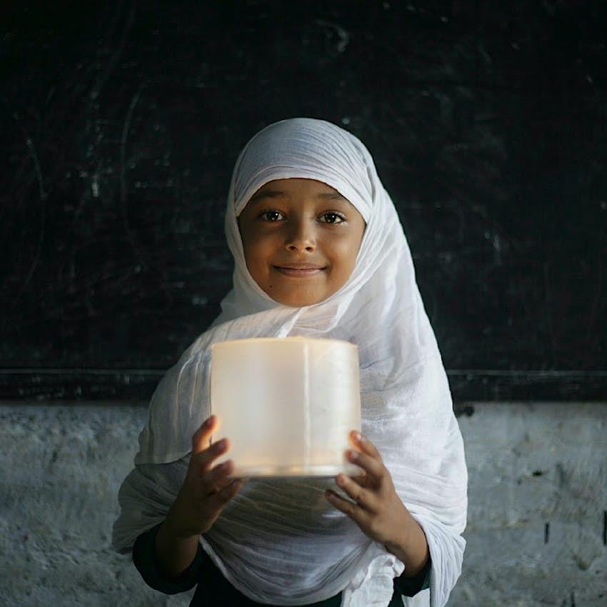 Girl holding an MPOWERD Luci light