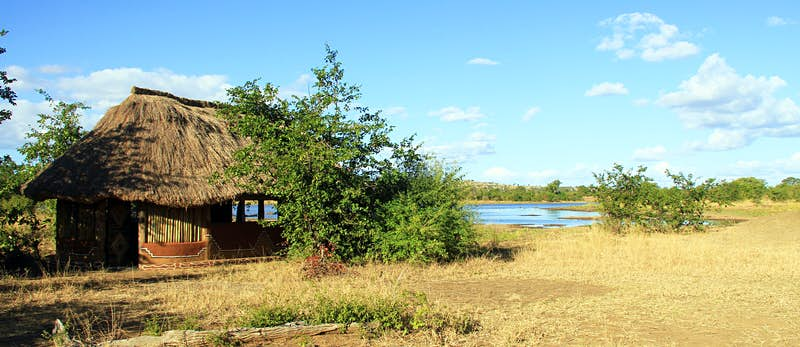 A thatched-roof, open-sided accommodation structure on the banks of a river; some trees shade the building.
