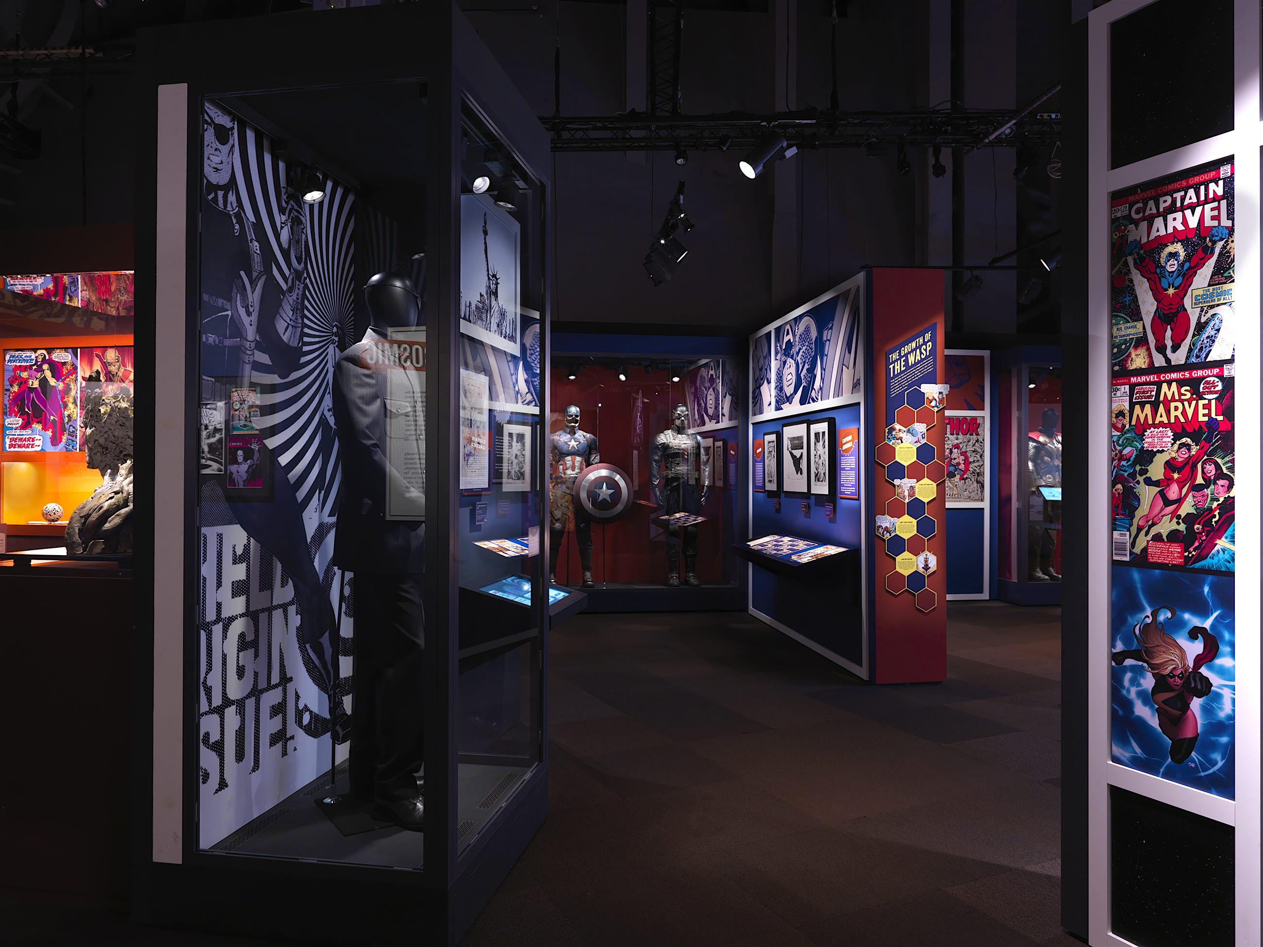 Revistas em quadrinhos, figurinos e adereços em exposição em uma exposição da Marvel
