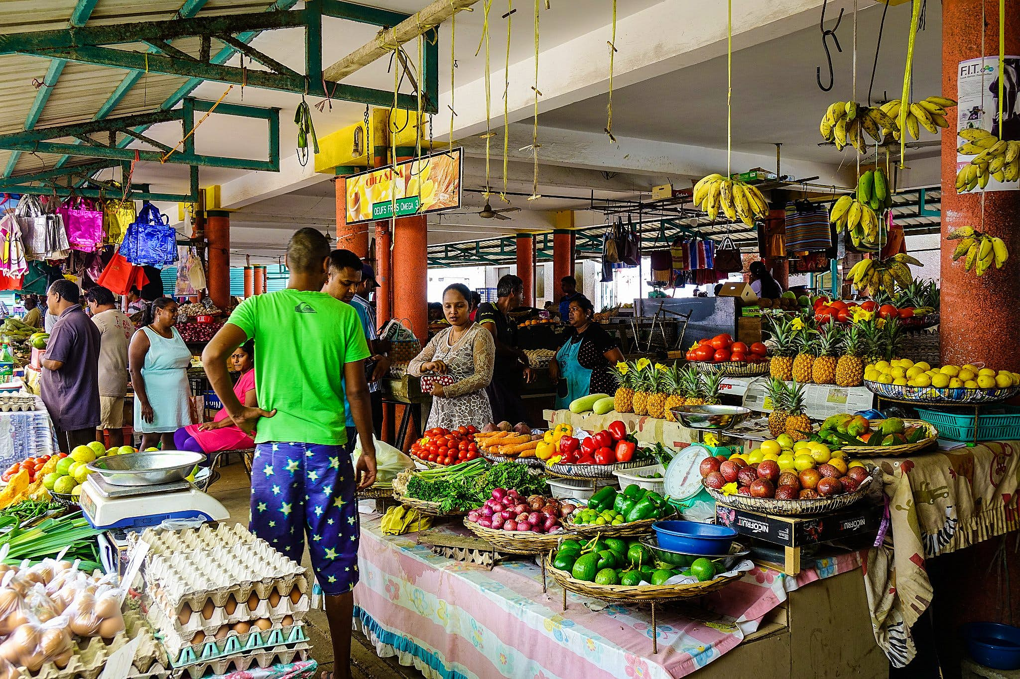 A Mauritius market, with people by a stall laden with colourful fresh produce.