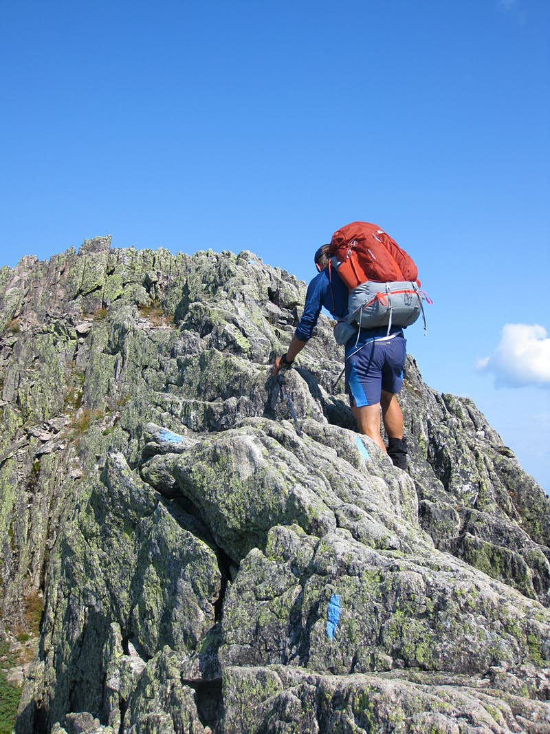 A man climbs down spiky rocks from the summit of Mount Katahdin in the Maine backwoods