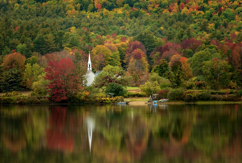 Red, orange and a few yellow trees punctuate the green foliage in New Hampshire as a white church steeple rises from among them and is reflected in a lake in the foreground; Autumn colors