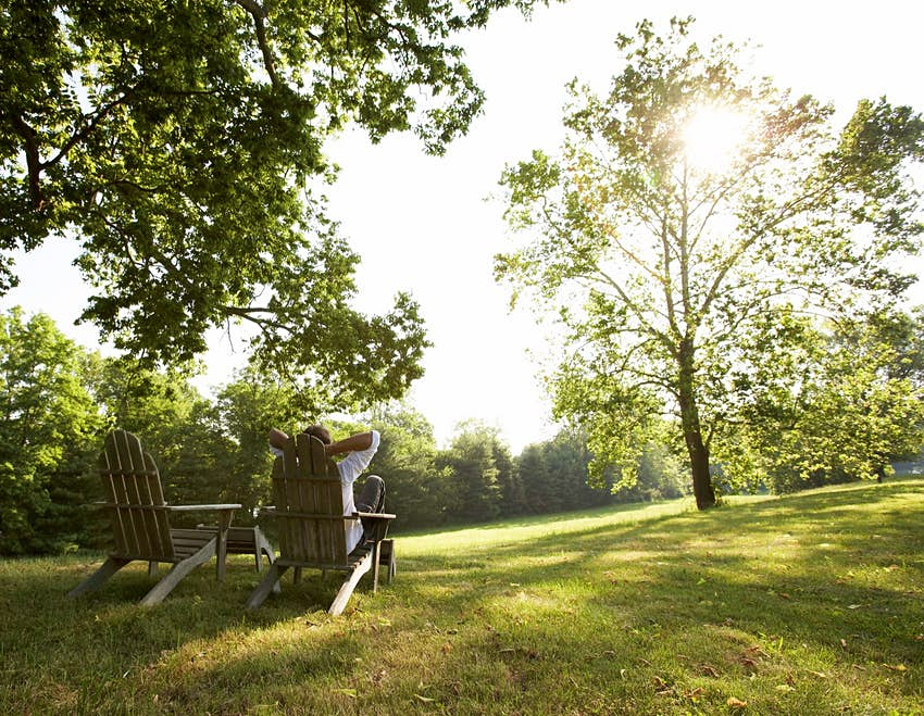 A man relaxes in a wooden chair on a grassy lawn