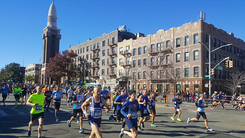 Marathon runners head down a wide-open boulevard in New York City under blue skies.