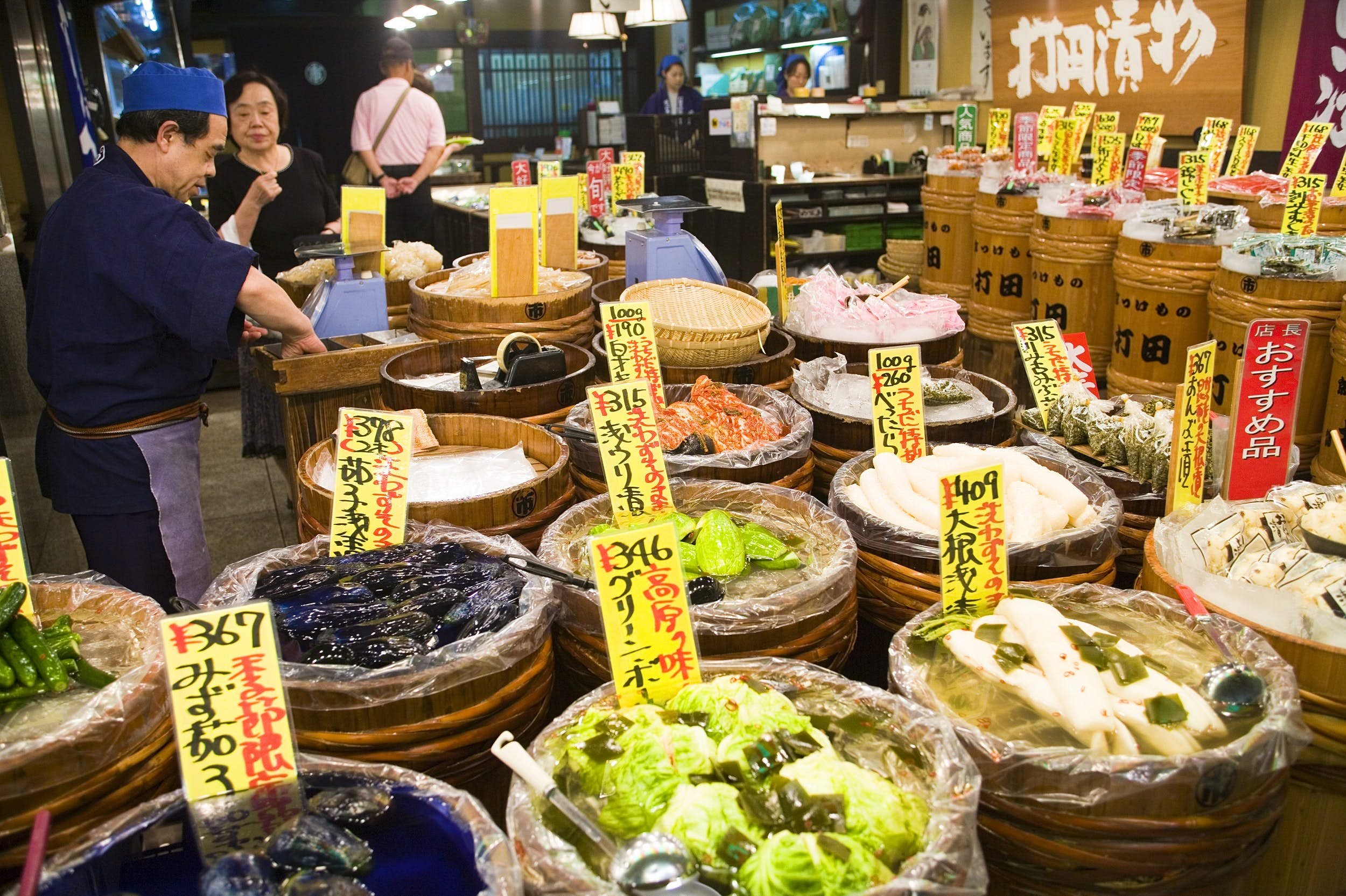 Numerous wooden tubs are filled with vegetables at the Nishiki Market; yellow labels with black-and-red Japanese writing denote the cost and contents of each.