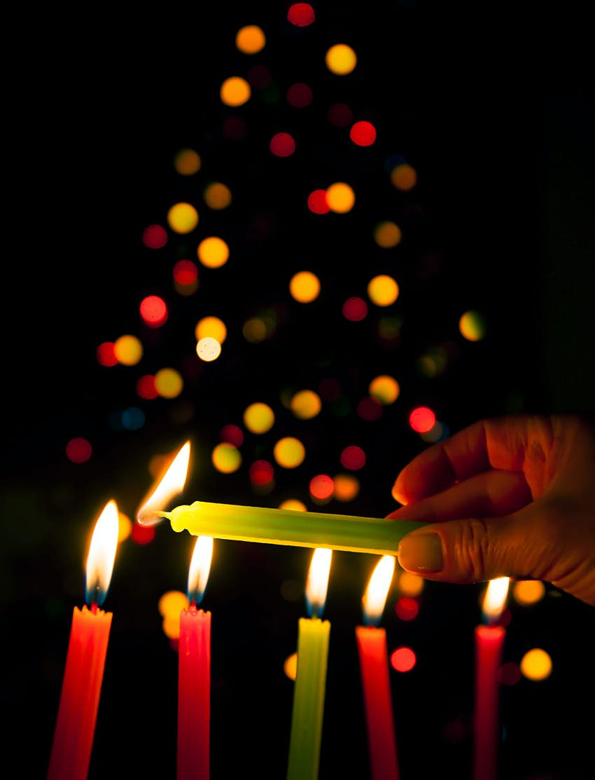 Noche de Velitas in Colombia. Multicoloured candles are lit in front of a Christmas tree, which is blurred in the background.