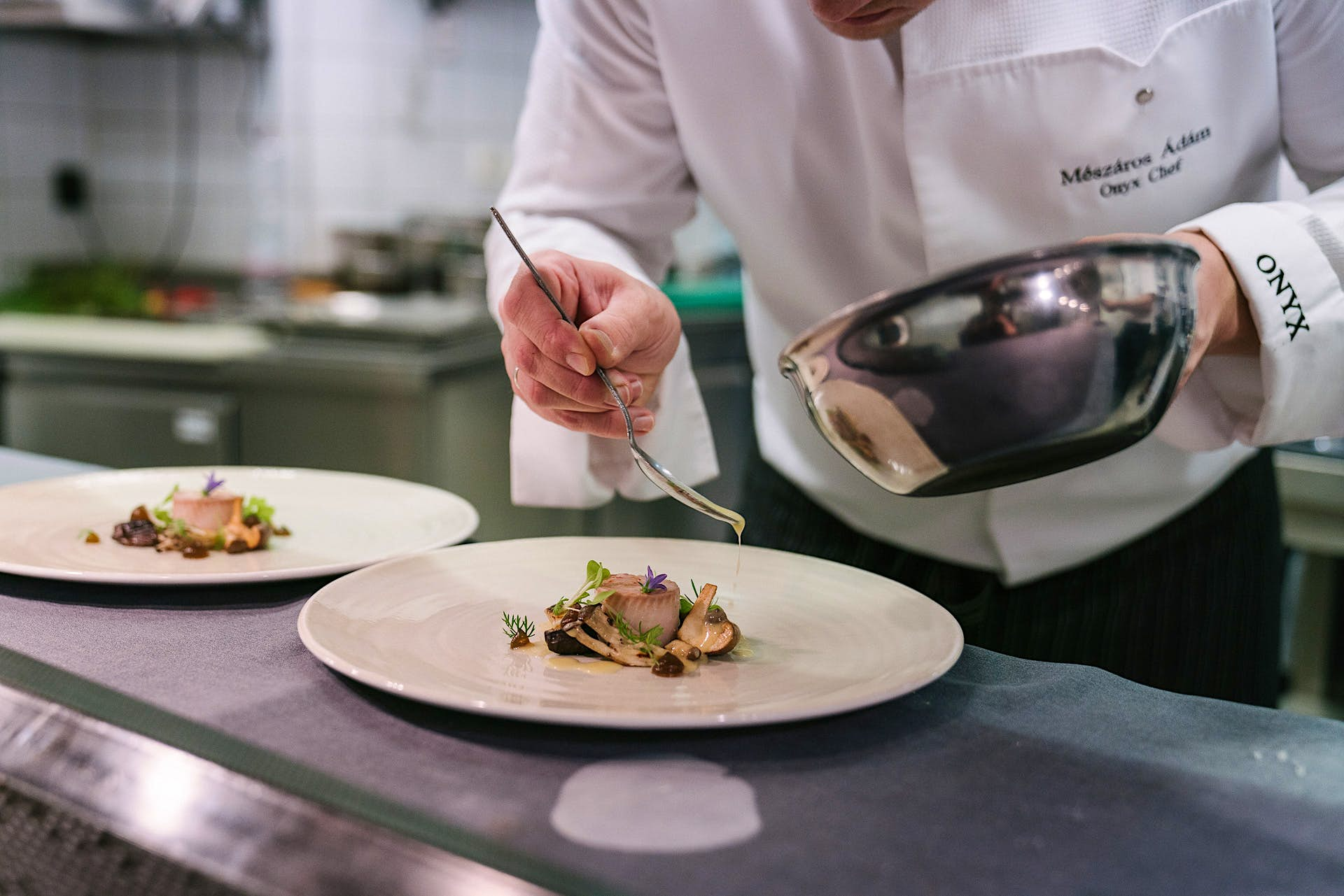 A chef at Onyx restaurant in Budapest, Hungary, is delicately spooning sauce over an exquisitely presented dish.
