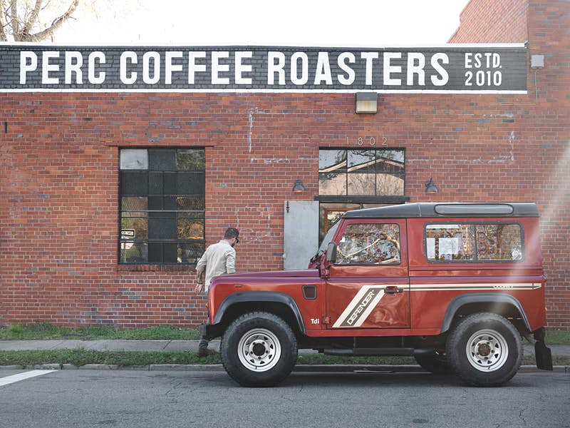 A red Land Rover Defender is parked in front of the red brick facade of Perc Coffee Roasters.