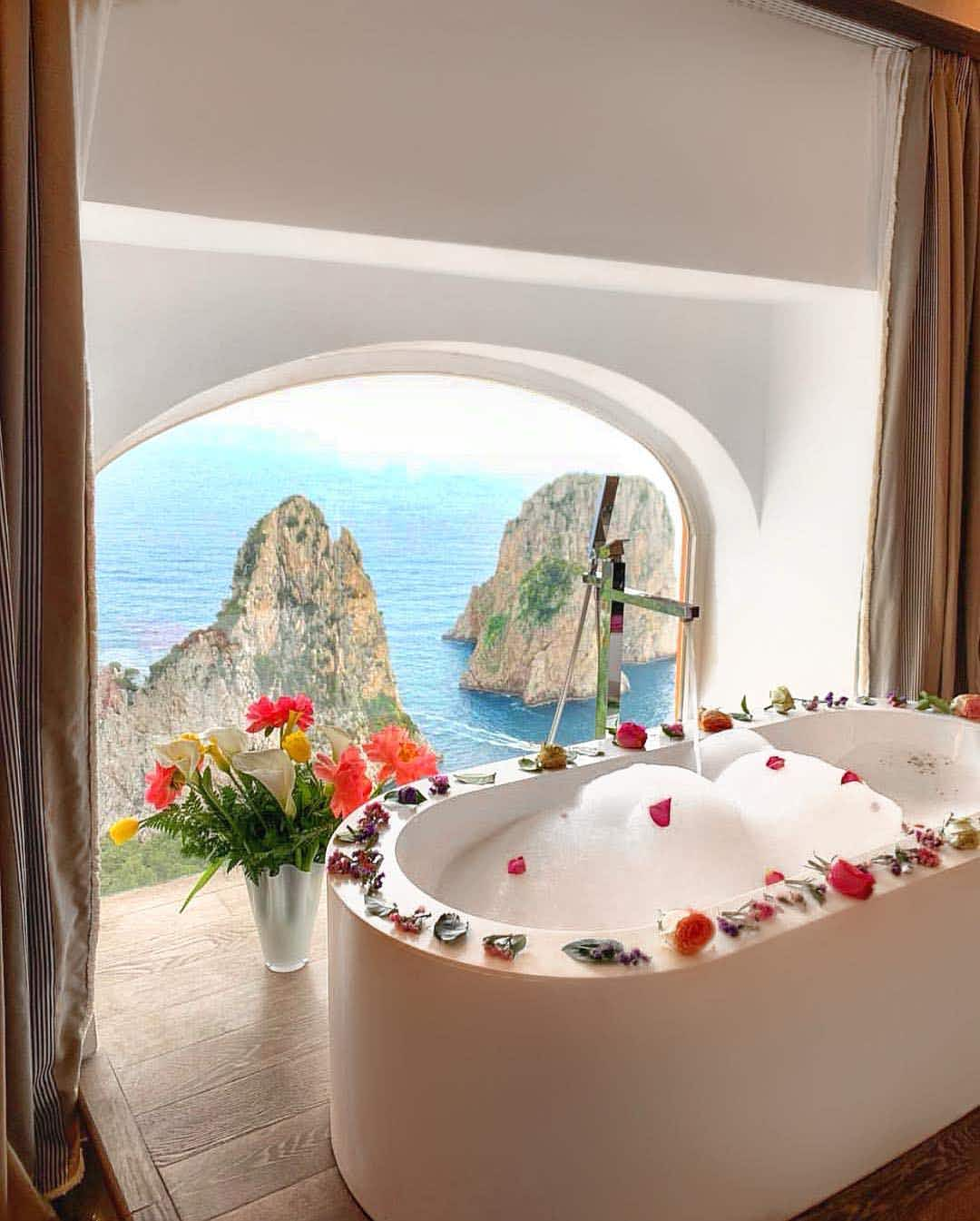 A white soaking tub filled with soap bubbles, with flower petals around the rim, in front of an arched window overlooking the water and rock formations, at Punta Tragara hotel