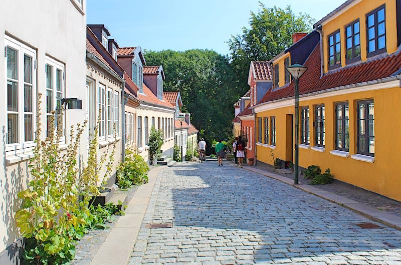 Vista para Paaskestræde, em Odense, na Dinamarca, uma rua idílica de paralelepípedos alinhada com casas coloridas.
