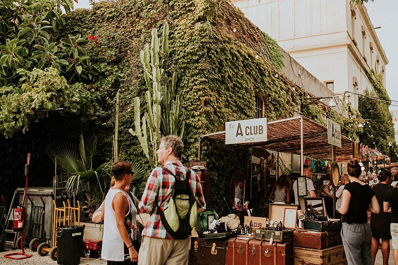 Shoppers browse a market stall full of vintage suitcases and other items, in front of a building clad in verdant foliage.
