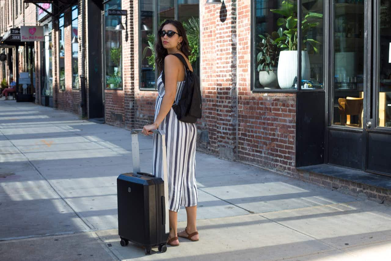 The wide aluminum handle attaches to the shell from the outside, giving travelers more packing room inside. Image © Phoenx