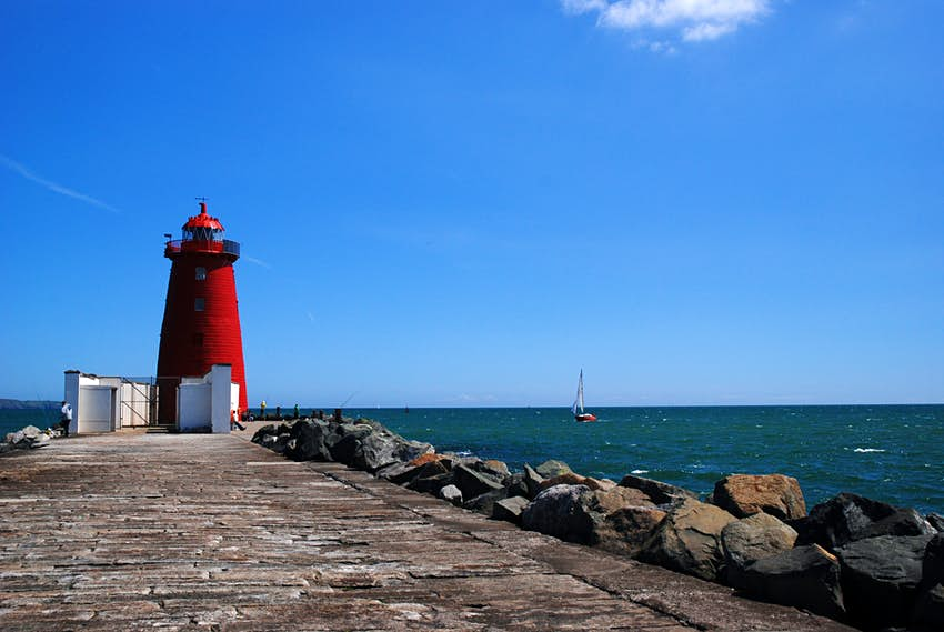A cobbled stone pathway on a bay leads to a bright red lighthouse in Dublin