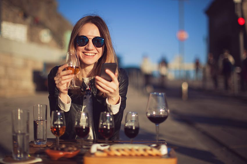 A smiling woman wearing sunglasses and holding her mobile phone and a glass of port sits at a table with various glasses of port; there is also a cheese board.