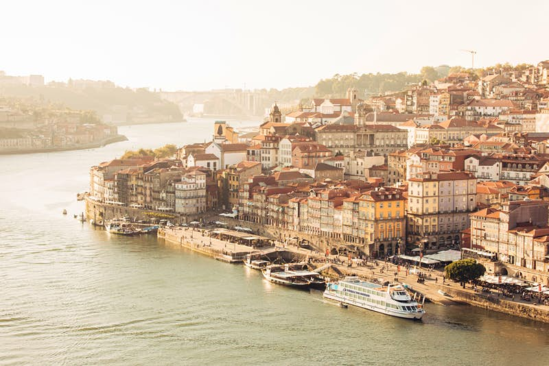 A shot from above looking down across the river to the historic centre of Porto, where centuries-old multi-storey buildings are crowded together and topped by terracotta-tiled roofs.