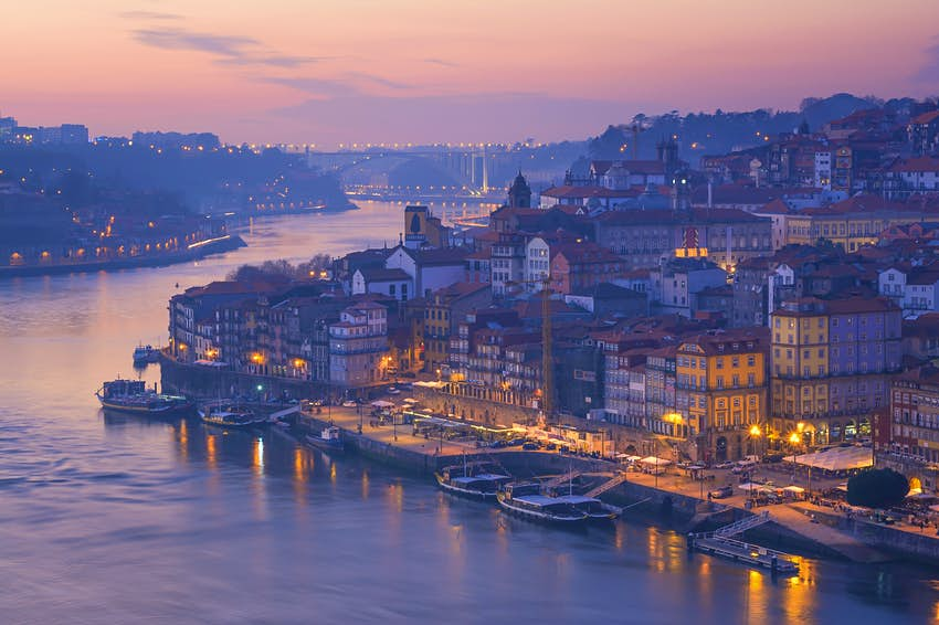 An image rich in pinks and purples shows the Douro River flowing past the historic Ribiera district, with its old buildings; in the distance is a large bridge crossing the river.