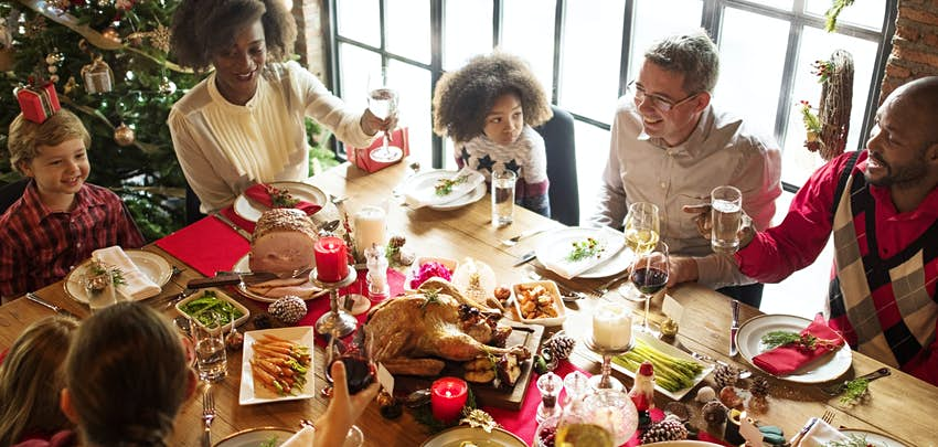 A family enjoying a réveillon meal in Quebec. The table is laden with roasted vegetables, a large turkey, decorations and drinks. Some people around the table are raising their glasses to each other, everyone is smiling and there is a Christmas tree in the background.