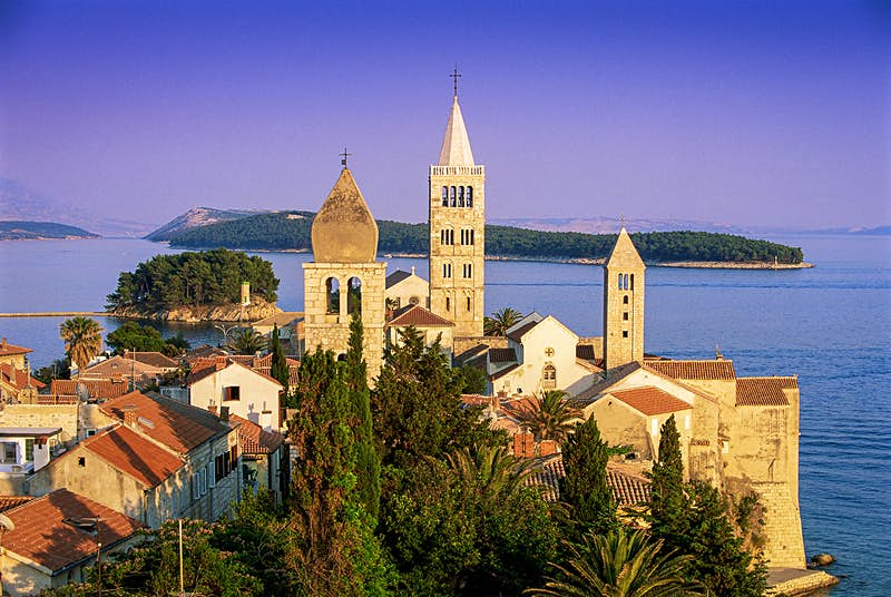 The historic spires of Rab at sunset, backed by the Kvarner Gulf.