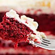 Extreme closeup of a bite of red velvet cake on a silver fork. In the background you can see the entire cake