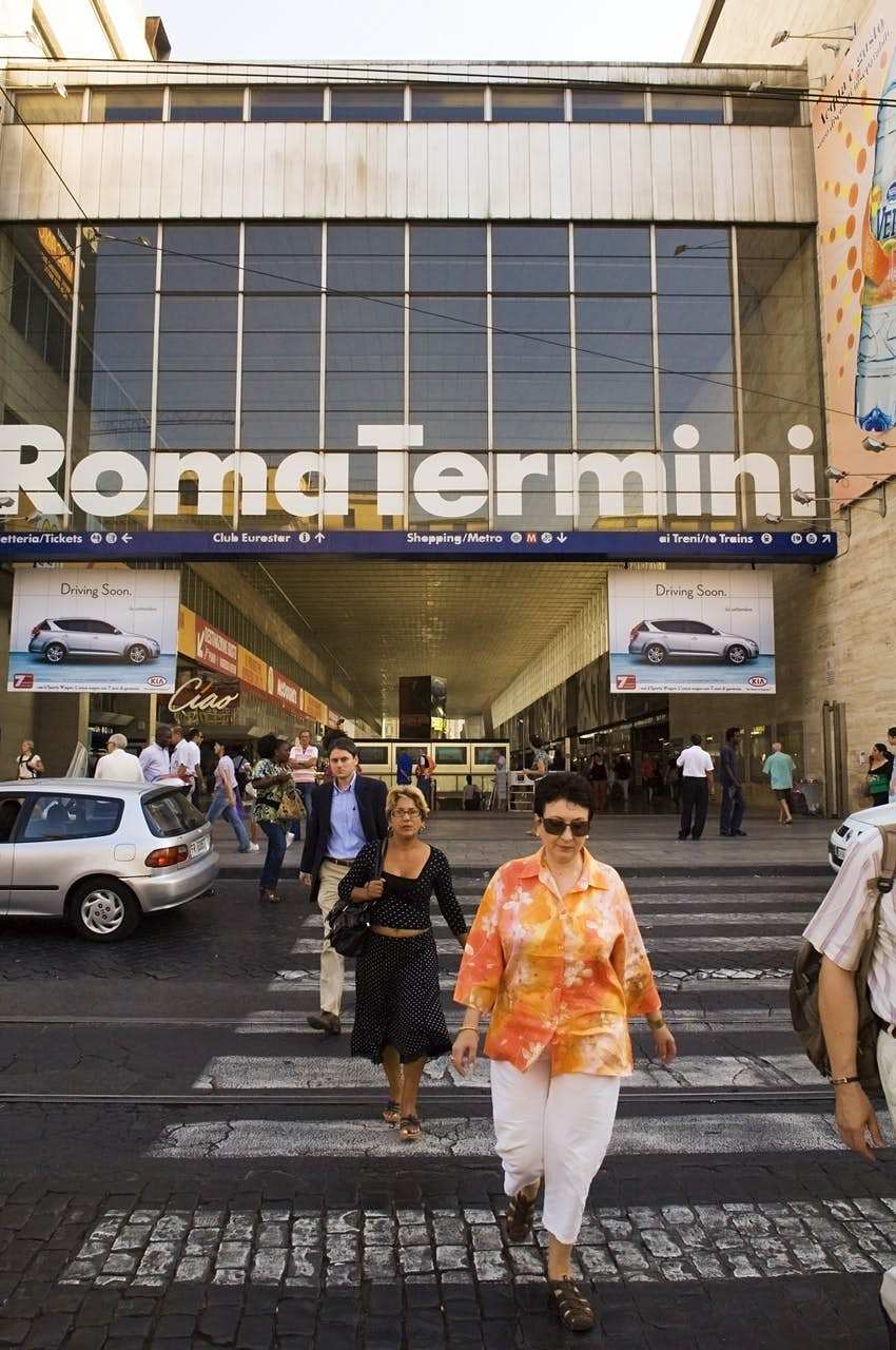 People walk across a zebra crossing in Rome towards the camera; behind them is a large building with huge glass windows with large white letters that read: Roma Termini