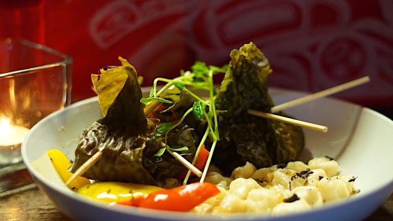A pair of green dumplings sit in a plate of vegetables; Indigenous food