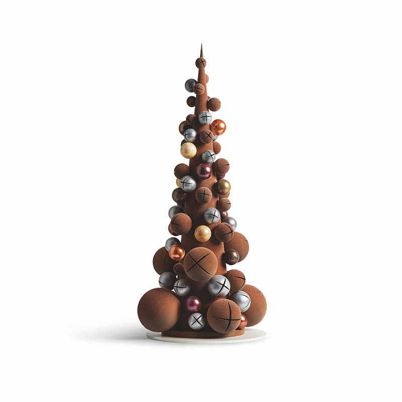 A tall, narrow Christmas tree constructed of chocolate balls and silver and gold jinglebells sits on a thin white platter against a white backdrop