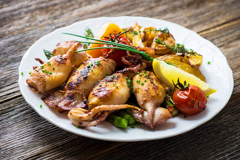 Grilled squid on a plate with lemon, tomato and asparagus