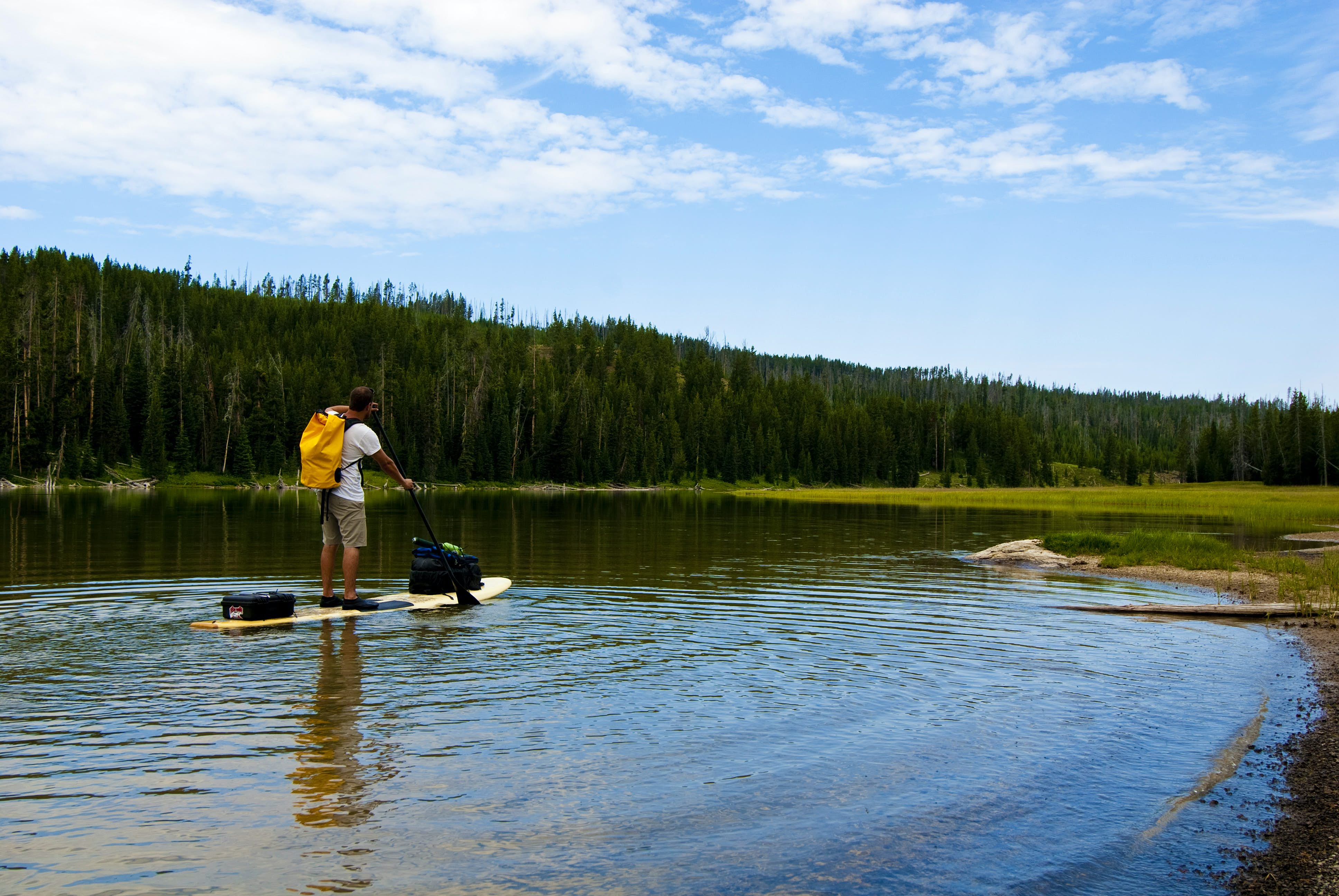 A stand-up paddleboarder on a lake in Yellowstone National Park