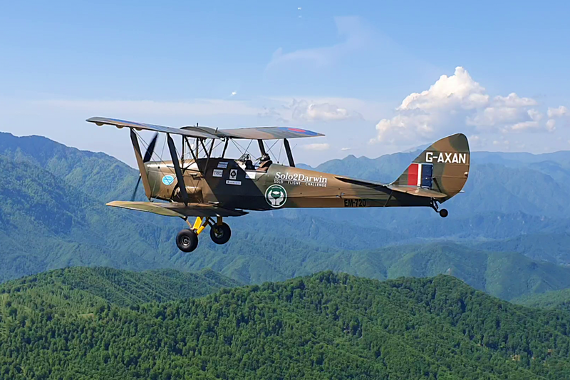 A Tiger Moth plane with 'Solo2Darwin' on the side flies over lush green hillsides