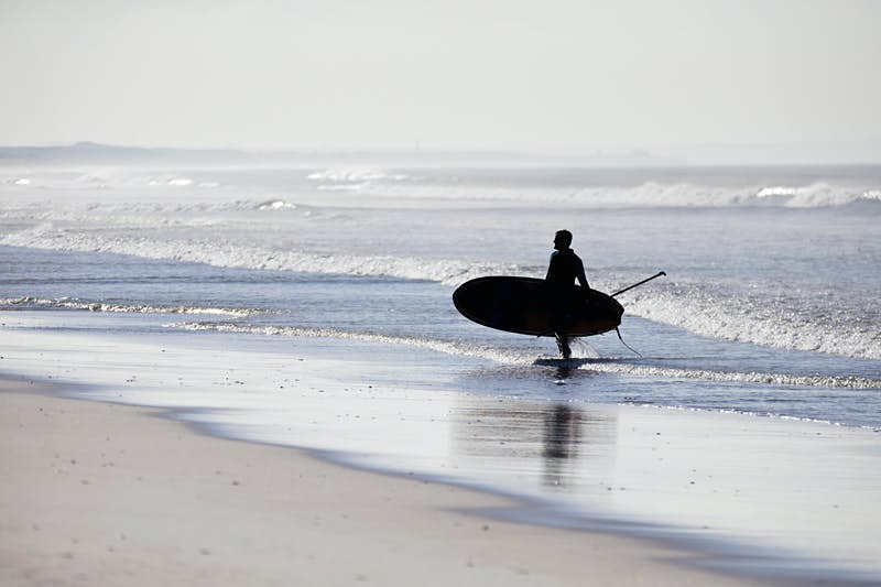 Paddleboarder walking out of ocean carrying paddleboard; places to go stand up paddle boarding