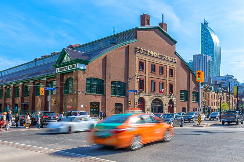 St Lawrence Market during the daytime. A motioned blurred Beck Taxi crosses the scene of the famous place. Free things to do in Toronto